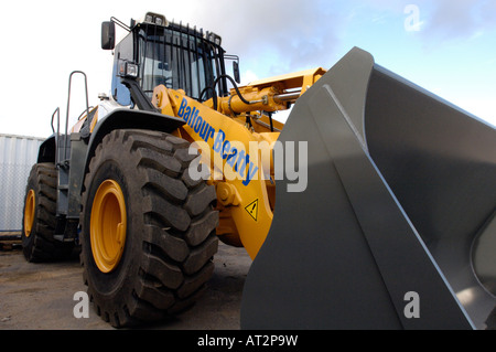 a large digger earth mover excavator jcb owned by balfour beatty construction on a building site with large wheel - Stock Photo