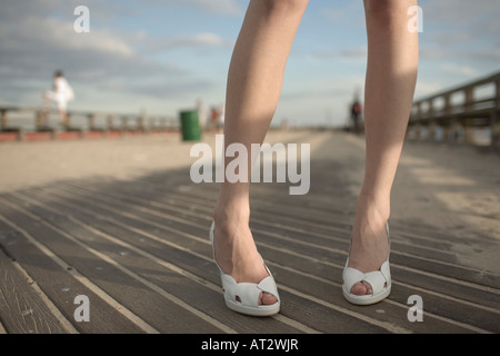 Young woman wearing white high heels and standing on the boardwalk at Coney Island Brooklyn - Stock Photo