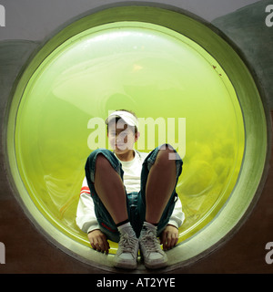 a young boy sitting in a big porthole - Stock Photo