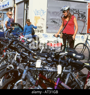 A woman buying a bicycle in Brick Lane flea market Sunday morning London UK - Stock Photo
