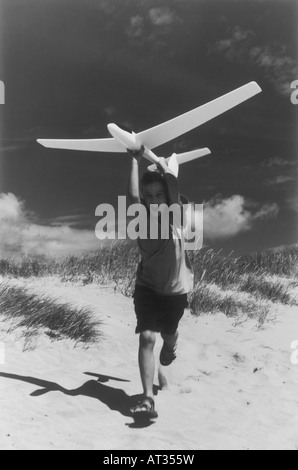 A boy running a long a beach with a model airplane - Stock Photo