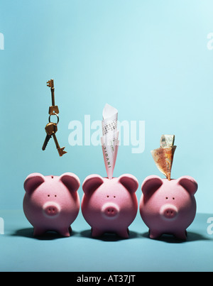 Three pink piggy banks in a row, money, keys and receipts - Stock Photo