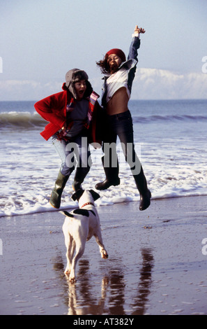 Two girls and a dog on a beach, girls jumping in the air - Stock Photo