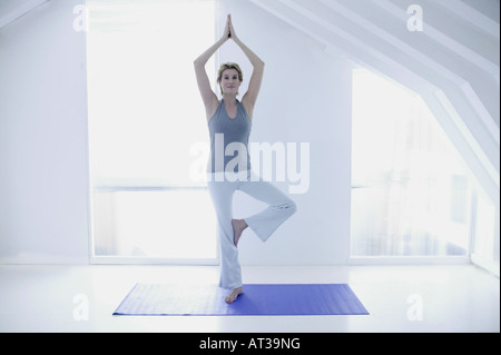A woman in her forties doing yoga - Stock Photo
