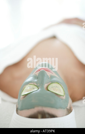 A woman relaxing in a face mask with cucumber over her eyes - Stock Photo