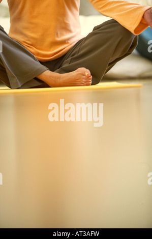A woman sitting crossed legged on a yoga mat, close-up - Stock Photo