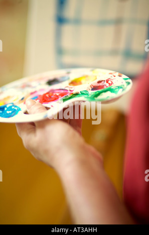 A female artist holding a paint palette, close-up - Stock Photo
