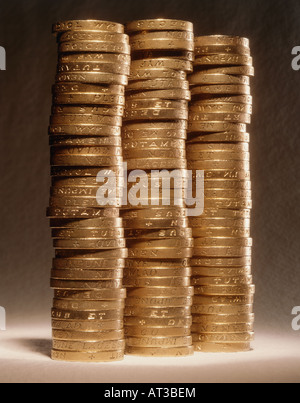 One pound coins stacked in three piles - Stock Photo