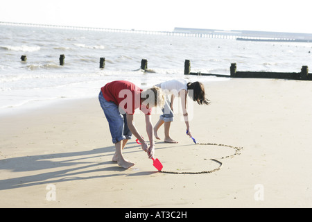 A young couple drawing a heart shape in the sand - Stock Photo