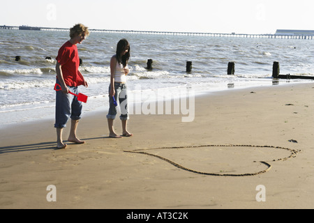 A young couple looking at a love heart they have drawn in the sand - Stock Photo