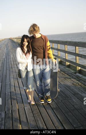 A teenage couple walking along an old pier, looking sad - Stock Photo