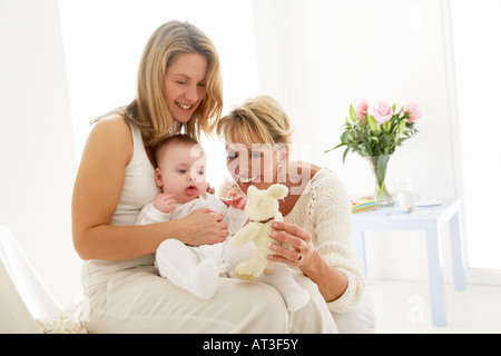 Baby sitting on mother's knee, grandmother holding cuddly toy - Stock Photo
