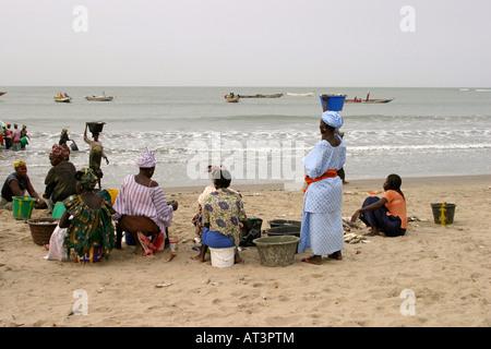 The Gambia Gunjur villagers awaiting return of fishing boats to unload - Stock Photo