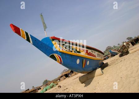 The Gambia Gunjur fishing painted prow of pirogue fishing boat on the beach - Stock Photo