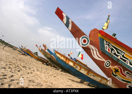 The Gambia Gunjur fishing painted prow of pirogues fishing boats on the beach - Stock Photo