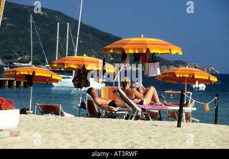 Holidaymakers sunbath on Biodola Beach under colorful sun umbrellas,Island of Elba. - Stock Photo