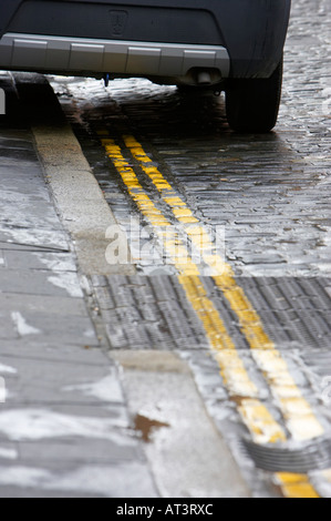 back of car parked on bright double yellow lines no parking road markings on old cobbled street - Stock Photo