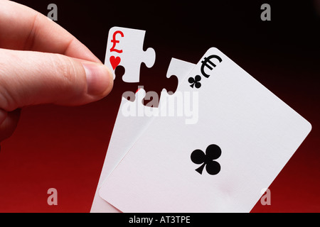 Man completing pair of playing cards showing currency symbols with jigsaw piece - Stock Photo