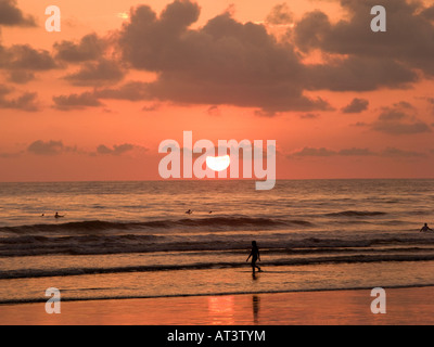 Costa Rica Dominical surfers in sea at sunset waiting for the days last waves - Stock Photo