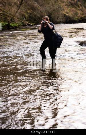 Photographer standing in river taking photographs - Stock Photo