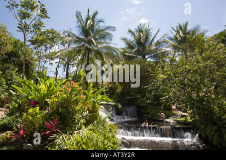 Costa Rica La Fortuna Tabacon Hot Springs resort guests sitting in pool between thermally heated waterfalls - Stock Photo