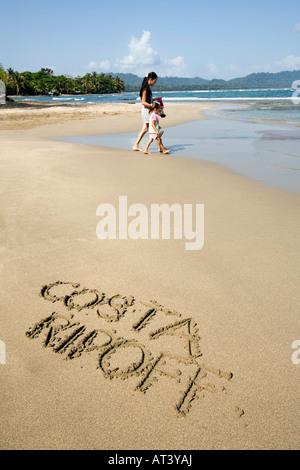 Costa Rica Caribbean Coast words Costa Ripoff written in sand on beach - Stock Photo