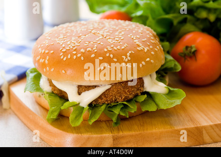 A hot chicken or fish burger & mayonnaise presented with fresh produce on a wooden platter - Stock Photo