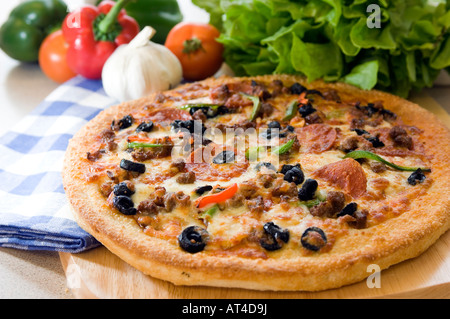 A hot Pizza pie presented with fresh produce on a wooden platter - Stock Photo