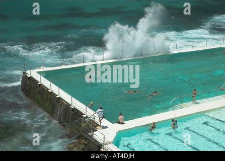 A wave breaks over the Bondi Icebergs pool, Bondi Beach, Sydney, New South Wales, Australia - Stock Photo