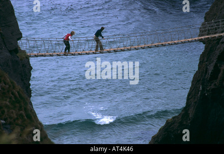 Two People on Carrick-A-Rede Rope Bridge County Antrim Northern Ireland - Stock Photo