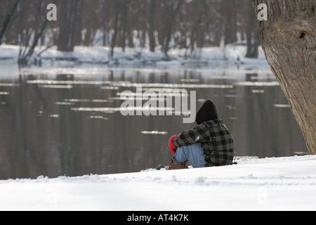 Lone person dressed for the winter cold sitting on a snow covered river bank - Stock Photo