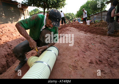 Poor communities building a sewerage system in their slum The government provides the materials - Stock Photo