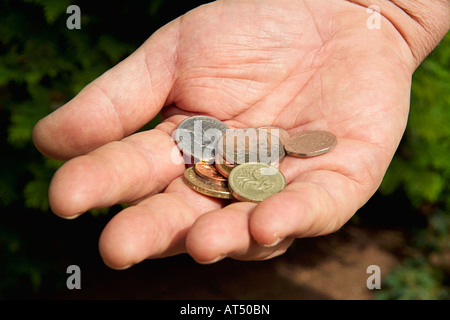 Close-up mans hand holding collection of uk coins - Stock Photo