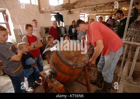 Demonstrating butter making in an old wooden churn llanerchaeron  Aberaeron ceredigion wales - Stock Photo