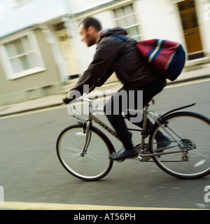 bearded beard wearing student cyclist with duffle bag in Oxford - Stock Photo