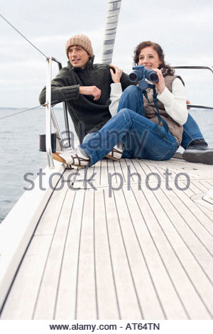 Germany, Baltic Sea, Lübecker Bucht, Young couple on boat, woman holding binoculars - Stock Photo