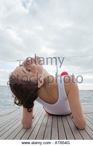 Germany, Baltic Sea, Lübecker Bucht, Young woman sitting on yacht, rear view - Stock Photo