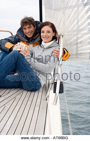 Germany, Baltic Sea, Lübecker Bucht, Young couple on sailing boat sitting and holding mugs - Stock Photo