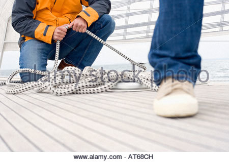 Germany, Baltic Sea, Lübecker Bucht, Man holding rope - Stock Photo