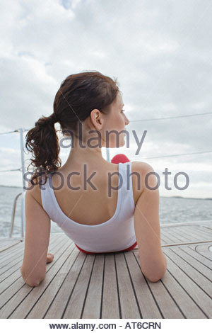 Germany, Baltic Sea, Lübecker Bucht, Woman sitting on yacht, rear view - Stock Photo