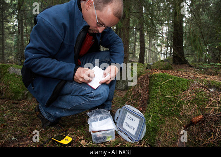 Middle aged man writing in the geocaching logbook in the forest Morby Uppsala Lan Sweden September 2007 - Stock Photo