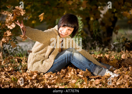 Germany, Bavaria, Young woman throwing autumn leaves, portrait - Stock Photo