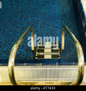 steps leading down to pool water lido handrail stainless steel water's edge blue top down view - Stock Photo
