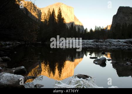 Sunrise illuminates El Capitan and its reflection in a still river at the Yosemite Valley. - Stock Photo