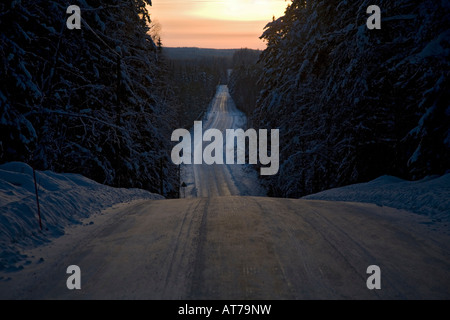 Scene of an empty, icy country road through forest at Winter at evening Finland - Stock Photo