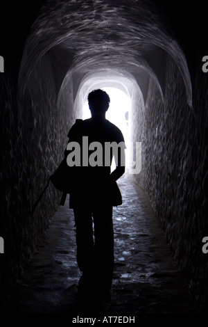 A man walks down a hall in Elmina Castle on a tour of the former slave fort - Stock Photo