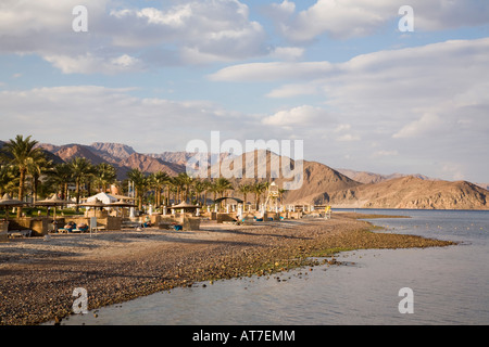 View along sandy beach to rugged hills on Red Sea coast with people sunbathing in late afternoon sunshine Taba Heights - Stock Photo