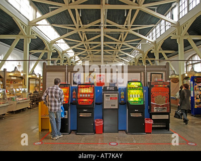 man playing games with slot machines in the market hall of the town Kuopio in Finland - Stock Photo