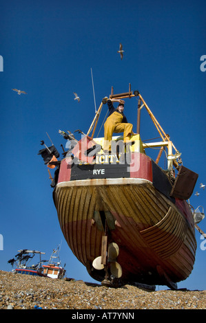 A crewman in oilskins on a small wooden fishing boat ashore on the beach at Hastings Sussex - Stock Photo
