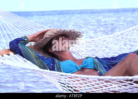 Woman wearing a straw hat relaxes in a hammock near the sea. - Stock Photo